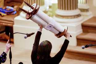 Rabbi Jacqueline Mates-Muchin holds a Torah scroll aloft during Shabbat morning service at Temple Sinai in Oakland, Calif. The California Department of Public Health released Monday a framework under which county health departments can approve the reopening of churches, mosques, synagogues and other houses of worship that have mostly shuttered their doors since Gov. Gavin Newsom's March stay-at-home order designed to slow the spread of the coronavirus.