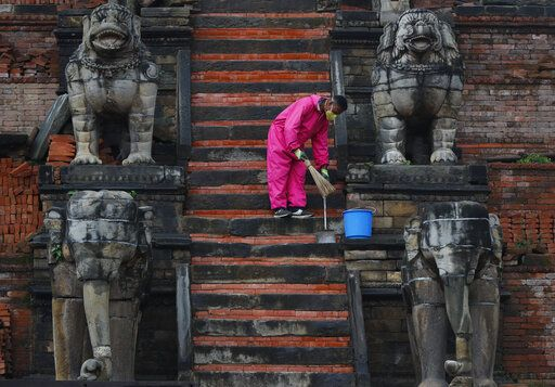 A Nepalese cleaner sweeps the stairs of temple during lockdown in Bhaktapur, Nepal, Tuesday, May 26, 2020. Nepal's lockdown imposed on March 24 to stop the spread of the coronavirus has been extended to June 2.