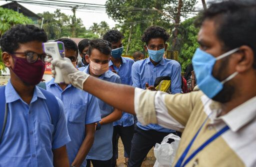 School children wearing masks get their hands sanitized and temperatures checked as they arrive to appear for state board examination during the coronavirus pandemic in Kochi, Kerala state, India, Tuesday, May 26, 2020.