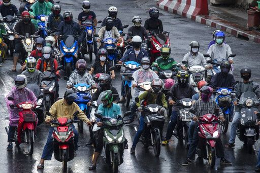 Motorcycles wearing face masks to help curb the spread of the new coronavirus wait at a stoplight in Bangkok, Thailand, Tuesday, May 26, 2020.