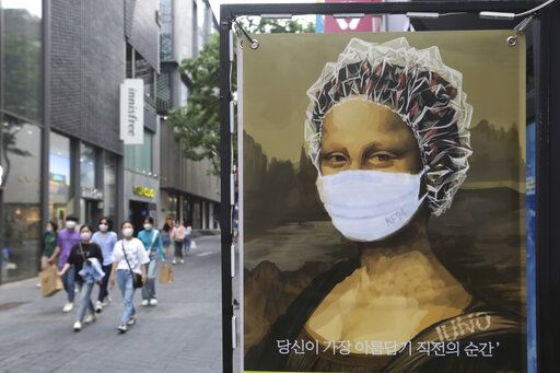 People wearing face masks to help protect against the spread of the new coronavirus walk by an advertisement of a hair shop at a shopping district in Seoul, South Korea, Tuesday, May 26, 2020.