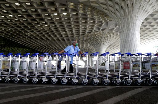 Airport staff push trollies at Chhatrapati Shivaji International Airport after domestic flights resume operations after nearly two-month lockdown amid the COVID-19 pandemic in Mumbai, India, Monday, May 25, 2020.