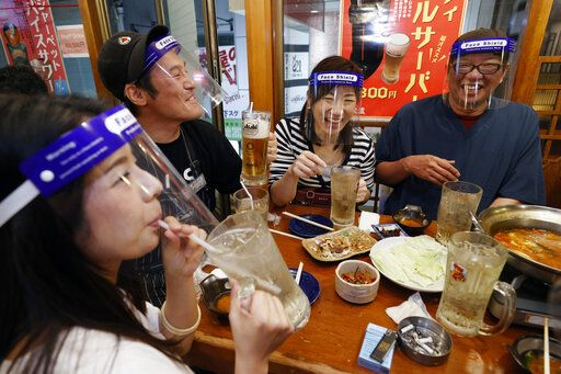 People wearing face shield, eat together at a pub in Osaka, western Japan Monday, May 25, 2020 as Japan has lifted the coronavirus state of emergency in Osaka and the two neighboring prefectures of Kyoto and Hyogo.  (Suo Takekuma/Kyodo News via AP)