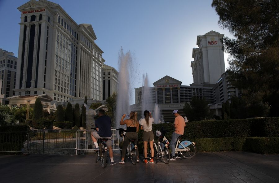 People stop to look at the fountains at Caesars Palace hotel and casino along the Las Vegas Strip devoid of the usual crowds during the coronavirus pandemic, Tuesday, May 26, 2020, in Las Vegas.