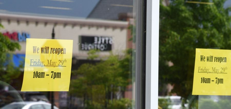 Signs in a storefront announce their reopening date at The Arboretum of South Barrington.