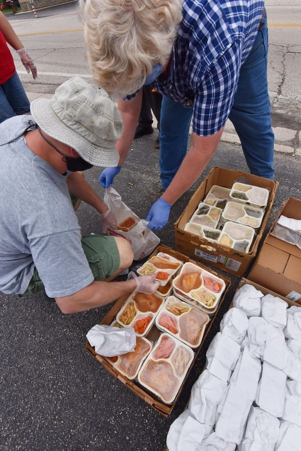 "Jim Miller and Eric Beccelli pack microwaveable meals that they donate every Thursday through the ""Grub Grab Pop-up Food Pantry"" they've created at the Long Lake Metra station."