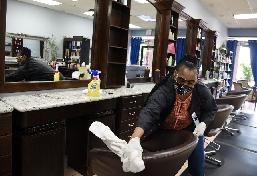 Rick West/rwest@dailyherald.comHair stylist Tanya Walker wipes down her station at PH Salon Wednesday in preparation for Friday's opening. She said she'll be wiping it down between each customer and then sealing the towel, her smock and the customer's robe in a bag to be washed. They'll be doing the same thing each time they take a customer to the wash basin or if the restroom is used