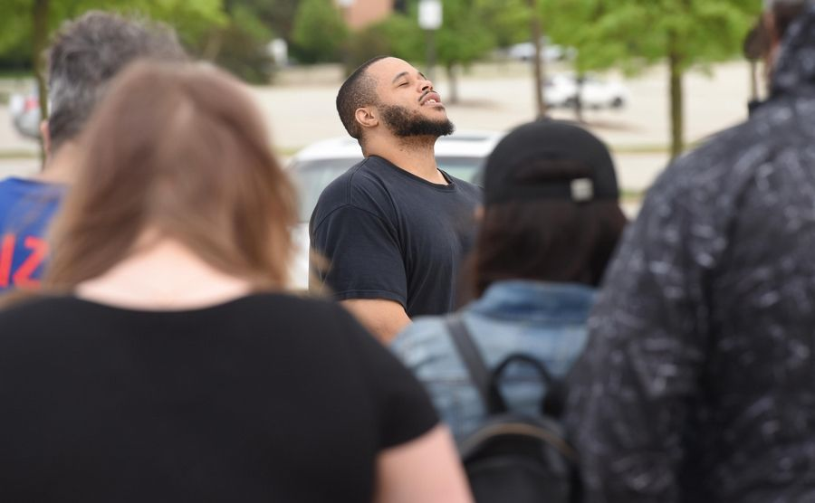 Reggie Hurdle of Schaumburg closes his eyes during a moment of silence before a Walk for Justice he organized on Golf Road in Schaumburg Friday evening.