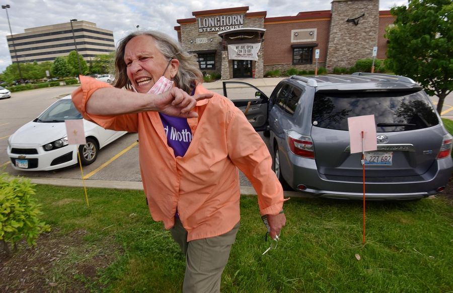 Donna M. Wattenbarger of Wheeling implores the Walk for Justice crowd to be passionate as they rally on Golf Road in Schaumburg Friday evening. She was picking up a meal at a nearby restaurant when the march got her attention and she briefly joined.