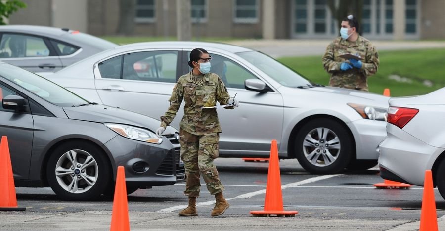 Members of the Illinois National Guard work with the public at the state's new drive-through COVID-19 testing facility at Rolling Meadows High School recently.