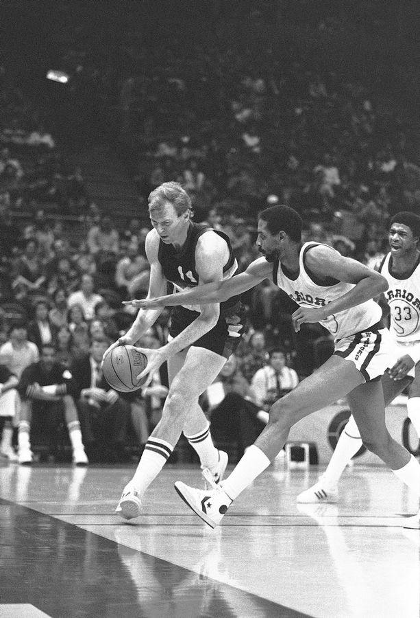 Denver's Dan Issel left, scoops up the ball as Golden State's Mickey Johnson tries to get it back during the first quarter of their NBA game in Oakland on Tuesday, Dec. 18, 1984.