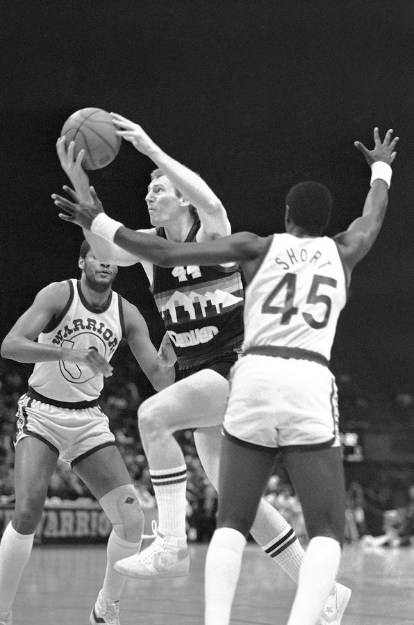 Denver Nuggets center Dan Issel drives to the basket around Golden State's Joe Barry Carroll left, and Purvis Short (45) to score his 26,000th career point during the first quarter of their NBA game in Oakland on Tuesday, Feb. 21, 1984.