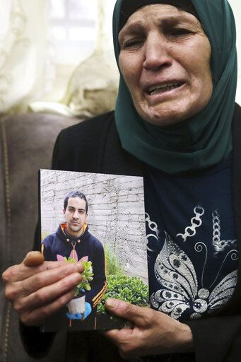 Rana, mother of Iyad Halak, 32, holds his photo at their home in East Jerusalem's Wadi Joz, Saturday, May 30, 2020. Israeli police shot dead a Palestinian near Jerusalem's Old City who they had suspected was carrying a weapon but turned out to be unarmed. A relative said Halak was mentally disabled and was heading to a nearby school for people with special needs.