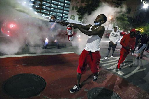 A man uses a fire extinguisher to protest the death of George Floyd, a handcuffed black man in police custody on Memorial Day in Minneapolis, Friday, May 29, 2020 in Indianapolis. The protest comes after a series of prominent black deaths that have inflamed racial tensions across the United States.(Jenna Watson/The Indianapolis Star via AP)