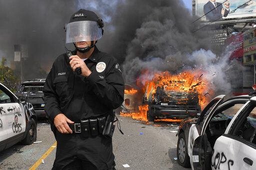 Los Angeles Police Department commander Cory Palka stands among several destroyed police cars as one explodes while on fire during a protest over the death of George Floyd, Saturday, May 30, 2020, in Los Angeles. Floyd died in police custody on Memorial Day in Minneapolis.