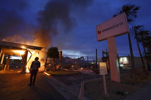 A man looks on as a bank burns after a protest over the death of George Floyd, Sunday, May 31, 2020, in La Mesa, Calif. Protests were held in U.S. cities over the death of Floyd, a black man who died after being restrained by Minneapolis police officers on May 25.