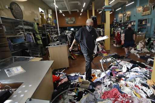 Terrel Ransom, center, store manager for Buffalo Exchange walks over clothes in the damaged store, Sunday, May 31, 2020, in Los Angeles, following a night of unrest and protests over the death of George Floyd, a black man who was in police custody in Minneapolis. Floyd died after being restrained by Minneapolis police officers on May 25.