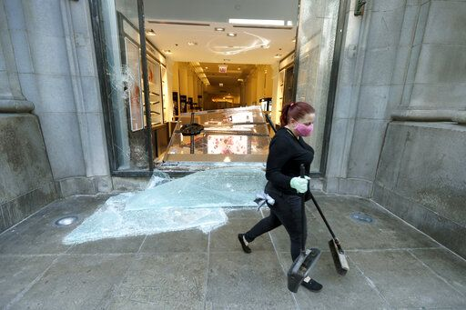 A volunteer worker walks past a shattered display window early Sunday morning, May 31, 2020, at the downtown Macy's store in Chicago, after a night of unrest and protests over the death of George Floyd, a black man who was in police custody in Minneapolis. Floyd died after being restrained by Minneapolis police officers on Memorial Day.