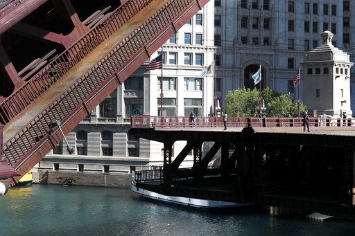 The curious venture out onto the edge of the northern half of the Michigan Avenue bridge Sunday, May 31, 2020, as all bridges across the Chicago River were closed Saturday night during a night of protests and vandalism in the city.