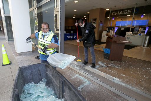 Clean up crews at a Chase Bank branch remove shattered glass early Sunday morning, May 31, 2020, in Chicago, after a night of unrest and protests over the death of George Floyd, a black man who was in police custody in Minneapolis. Floyd died after being restrained by Minneapolis police officers on Memorial Day.