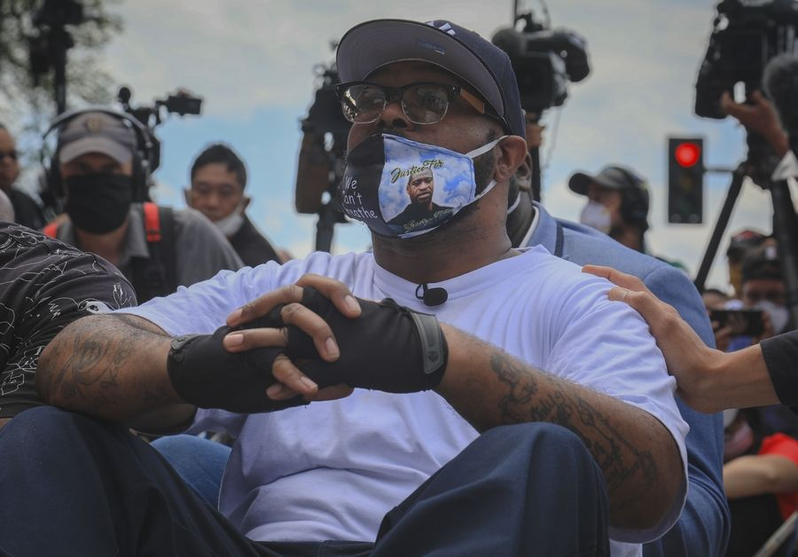 Terrence Floyd, brother of George Floyd, sits Monday at the intersection of 38th Street and Chicago Avenue in Minneapolis where George Floyd, encountered police and died while in their custody. An autopsy commissioned for George Floyd's family found that he died of asphyxiation due to neck and back compression.