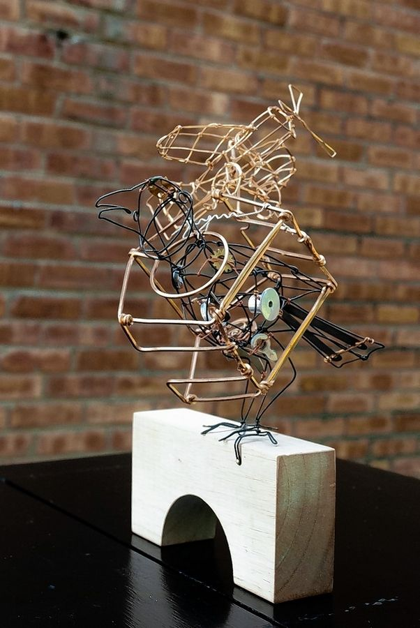 A mixed media sculpture by Tim Flynn. His wire sculptures often feature several sculptures within the main structure of the piece.
