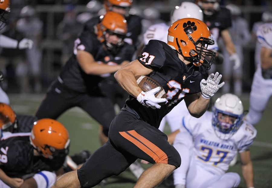 Wheaton Warrenville South senior Jake Arthurs (31) sweeps around the line of scrimmage in a football game against Wheaton North.
