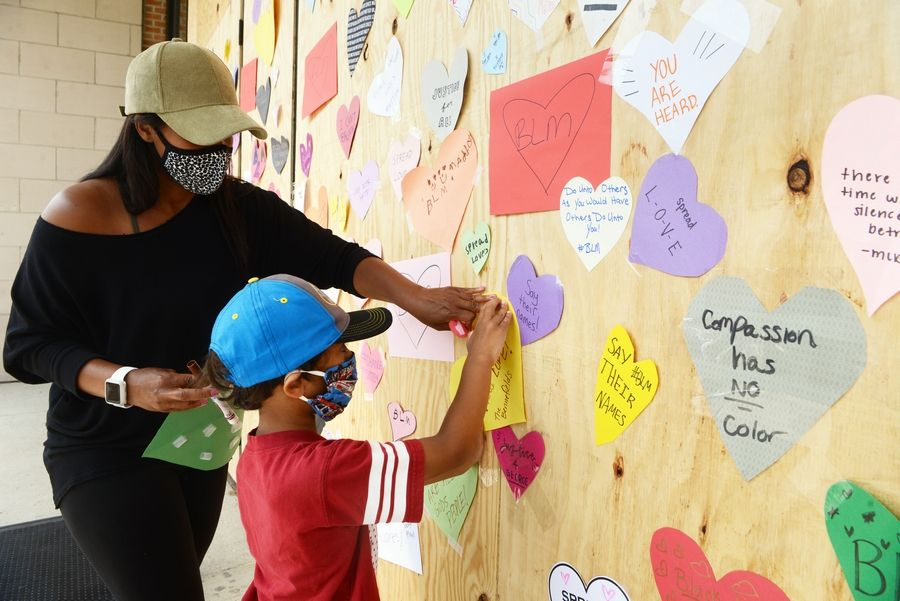 Brittany Bennefield and her son Maddox, 5, of Plainfield place a paper heart together on a downtown Naperville storefront as part of an effort that drew hundreds of people Wednesday, two days after instigators damaged roughly 30 stores after a protest.