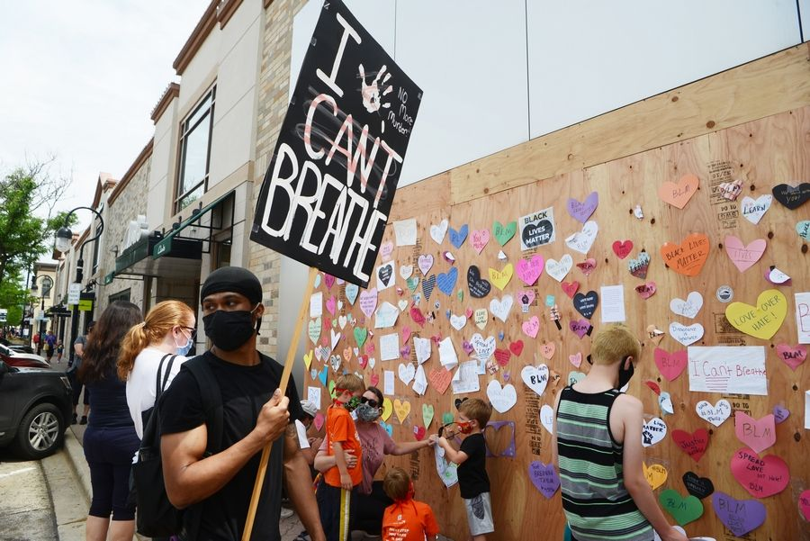 Devaughan Welch of Bolingbrook holds a sign Wednesday during an effort to post paper hearts with positive messages on businesses in downtown Naperville. Thirty businesses were damaged Monday night when a protest turned destructive.