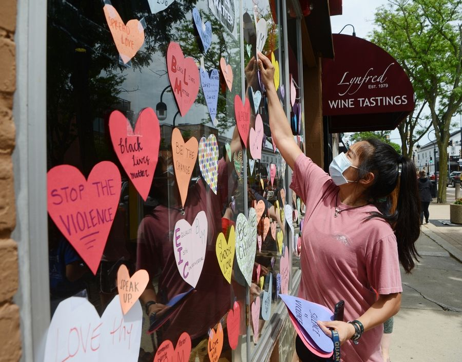 June Sun of Naperville places a paper heart among many others Wednesday during an effort to decorate downtown Naperville two days after 30 businesses there were damaged when a protest turned destructive.