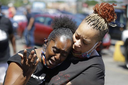 Two women pray, Tuesday, June 2, 2020, in Louisville, Ky., near the intersection where David McAtee was killed Sunday evening. Louisville police say video obtained from security cameras at McAtee's business and an adjoining business show that McAtee fired a gun as police and National Guard soldiers were enforcing a curfew approached his business.