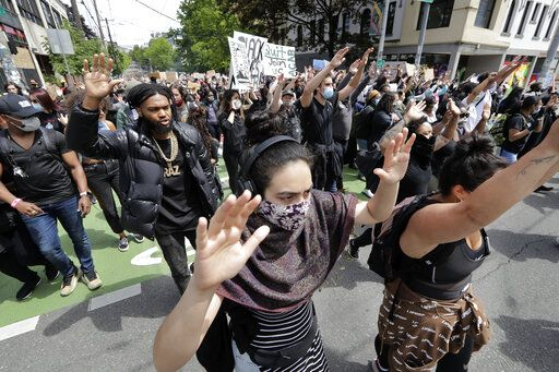 Demonstrators leave a rally and head toward Seattle City Hall Wednesday, June 3, 2020, in Seattle, following protests over the death of George Floyd, a black man who died in police custody in Minneapolis.