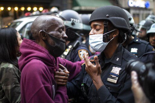 A protester and a police officer shake hands in the middle of a standoff during a solidarity rally calling for justice over the death of George Floyd Tuesday, June 2, 2020, in New York. Floyd died after being restrained by Minneapolis police officers on May 25.