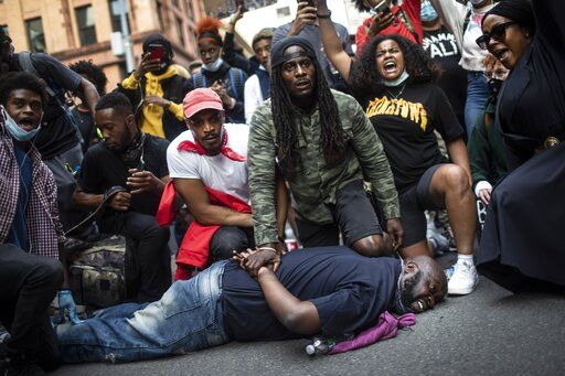 Protesters reenact the scene where George Floyd was restrained by police while marching in a solidarity rally calling for justice over the death of George Floyd Tuesday, June 2, 2020, in New York. Floyd died after being restrained by Minneapolis police officers on May 25.