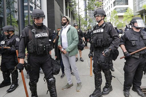 Activist David Lewis, center, walks past police officers as he heads in to Seattle City Hall to meet with the mayor Wednesday, June 3, 2020, in Seattle, following protests over the death of George Floyd, a black man who was in police custody in Minneapolis.