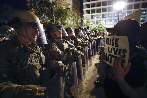 Utah National Guard soldiers line the street as demonstrators gather to protest the death of George Floyd, Wednesday, June 3, 2020, near the White House in Washington. Floyd died after being restrained by Minneapolis police officers.