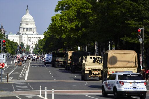 Demonstrators walk along Pennsylvania Avenue as a line of police and military vehicles drive as they protest the death of George Floyd, Wednesday, June 3, 2020, in Washington. Floyd died after being restrained by Minneapolis police officers.
