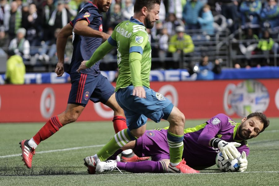 Chicago Fire goalkeeper Kenneth Kronholm, right, grabs the ball as Seattle Sounders midfielder Joao Paulo, center, closes in, during the first half of an MLS soccer match, Sunday, March 1, 2020, in Seattle.