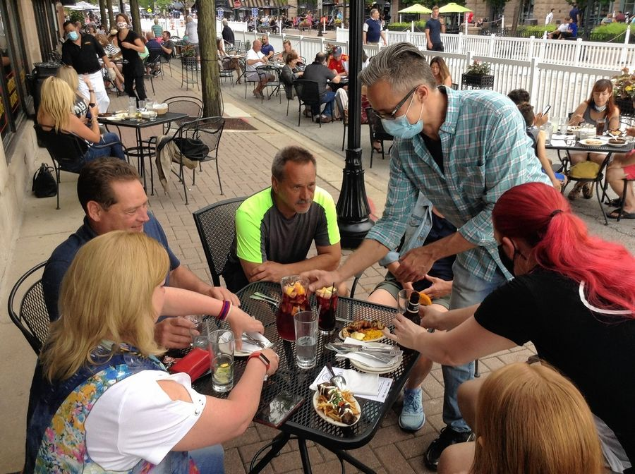 Danny Barbarigos, owner of La Tasca Tapas, serves sangria to the Crigler family, regulars who were among the first to dine there Wednesday night. It marked the first night of Arlington Heights' outdoor dining zone.