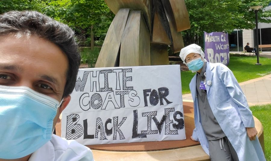 "Dr. Dhruvil Pandya, an interventional neuroradiology physician, and Dr. Morlie Wang, diagnostic radiology, show their support for the Black Lives Matter movement outside Northwestern Medicine Central DuPage Hospital with a sign that says, ""White Coats for Black Lives."""