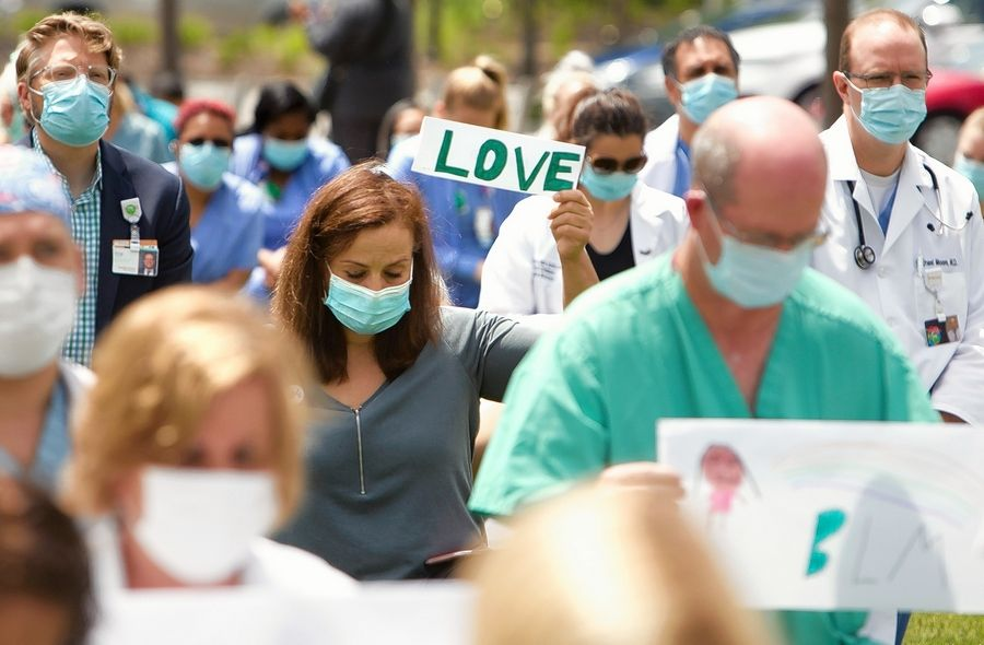Doctors, nurses and other staff members held up signs of peace and love as they knelt outside Elmhurst Hospital on Friday afternoon in solidarity with the Black Lives Matter movement.
