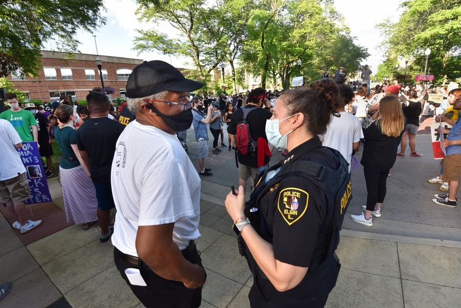 Charles Clements, whose daughter Decynthia was killed by an Elgin police officer in 2018, talks with Elgin Police Chief Ana Lalley and Deputy Police Chief Colin Fleury in front of city hall after a Black Lives Matter march Friday night from Kiwanis Park.