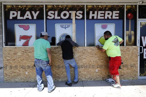 Workers board up windows at a store Tuesday, June 2, 2020, in Chicago. Chicago's Cicero neighborhood was vandalized last Monday amid protests sparked by the death of George Floyd, who died in police custody in Minneapolis on May 25..