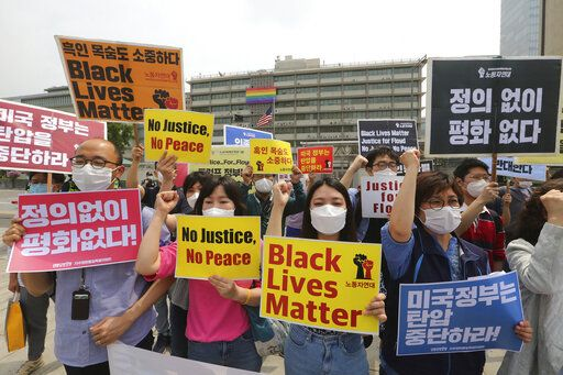 "South Korean protesters shout slogans during a protest over the death of George Floyd, a black man who died after being restrained by Minneapolis police officers on May 25, near the U.S. embassy in Seoul, South Korea, Friday, June 5, 2020. The signs read ""The U.S. government should stop oppression and there is no peace without justice."""