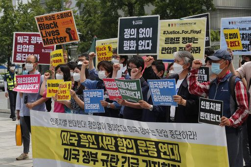 "South Korean protesters shout slogans during a protest over the death of George Floyd, a black man who died after being restrained by Minneapolis police officers on May 25, near the U.S. embassy in Seoul, South Korea, Friday, June 5, 2020. The signs read: ""The U.S. government should stop oppression and There is no peace without justice."""