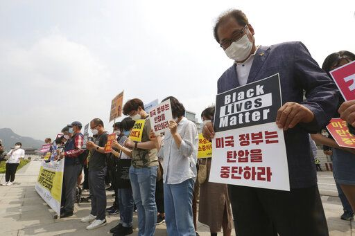 "South Korean protesters take a moment of silence during a protest over the death of George Floyd, a black man who died after being restrained by Minneapolis police officers on May 25, near the U.S. embassy in Seoul, South Korea, Friday, June 5, 2020. The signs read ""The U.S. government should stop oppression and there is no peace without justice."""