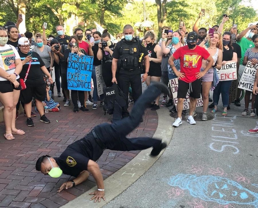 Elgin police officer Hector Gutierrez break dances at the Elgin In Solidarity With Black Lives Matter rally Friday night in front of Elgin City Hall.