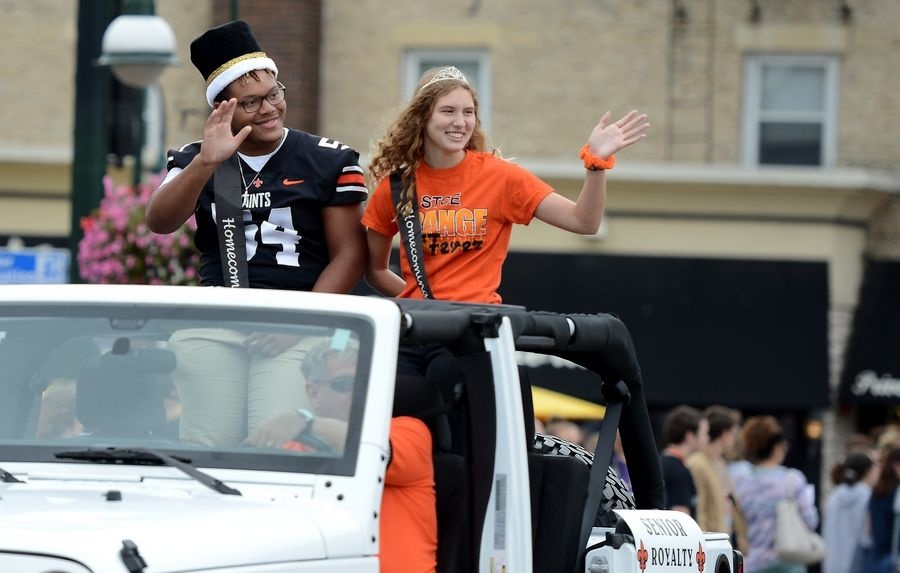Homecoming king and queen Jalen Farmer and Alexis Hydar wave to folks on the bridge while riding in the St. Charles East High School homecoming parade in downtown St. Charles.