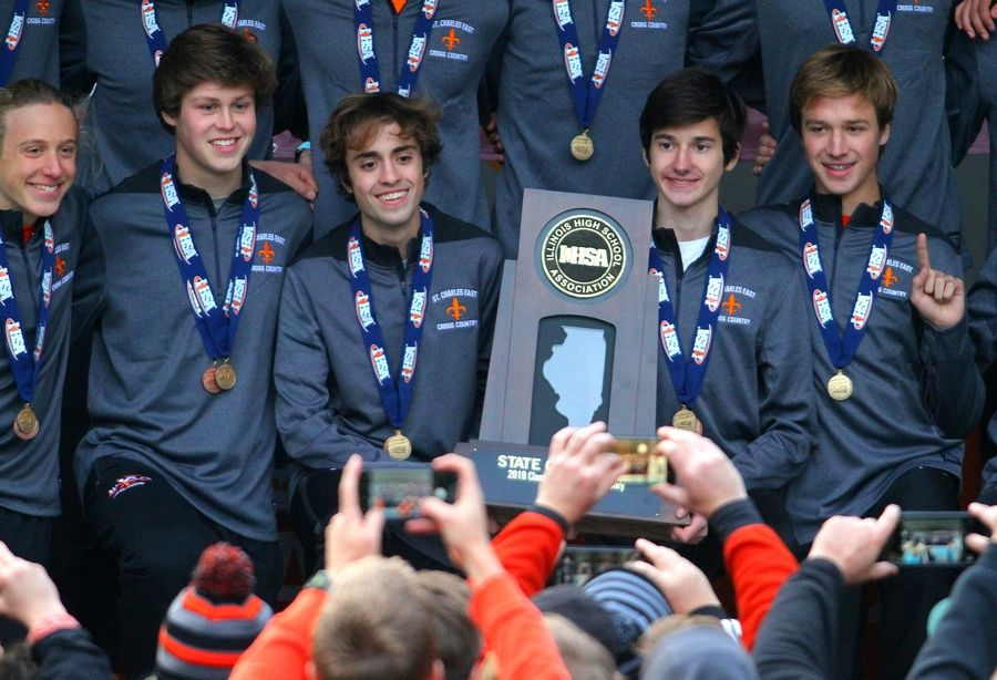 Left to right: St. Charles East's Micah Wilson, Luke Schildmeyer, Aidan King, Bob Liking and Zack Loomis pose with the team's state championship trophy on Saturday during the IHSA State Cross Country Finals awards ceremony. The Saints won this year's Class 3A boys title.