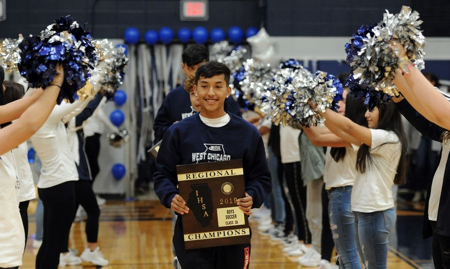 West Chicago's Cheche Morfin holds on of the team's Class 3A championship plaques as the team is cheered on during a pep assembly at West Chicago High School before going on to win the state championship, the school's first in any sport since 1974.